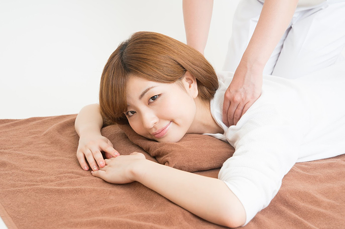 施術台に寝転びスタッフに肩を押されている女性
