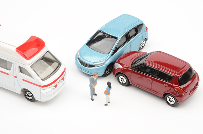 衝突している自動車2台と救急車と人の小さな模型