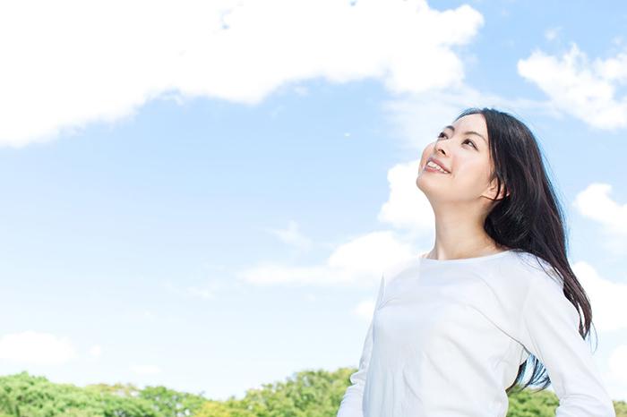 晴天の下にいる笑顔の女性