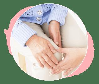 膝を抑えている患者の手とその膝に触れているスタッフの手